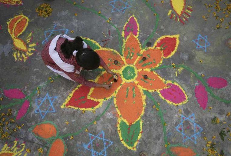 Een schoolkind in Jammu maakt rangoli, traditionele versieringen van bloemen, gemaakt van gekleurd poeder.<br /> Beeld null