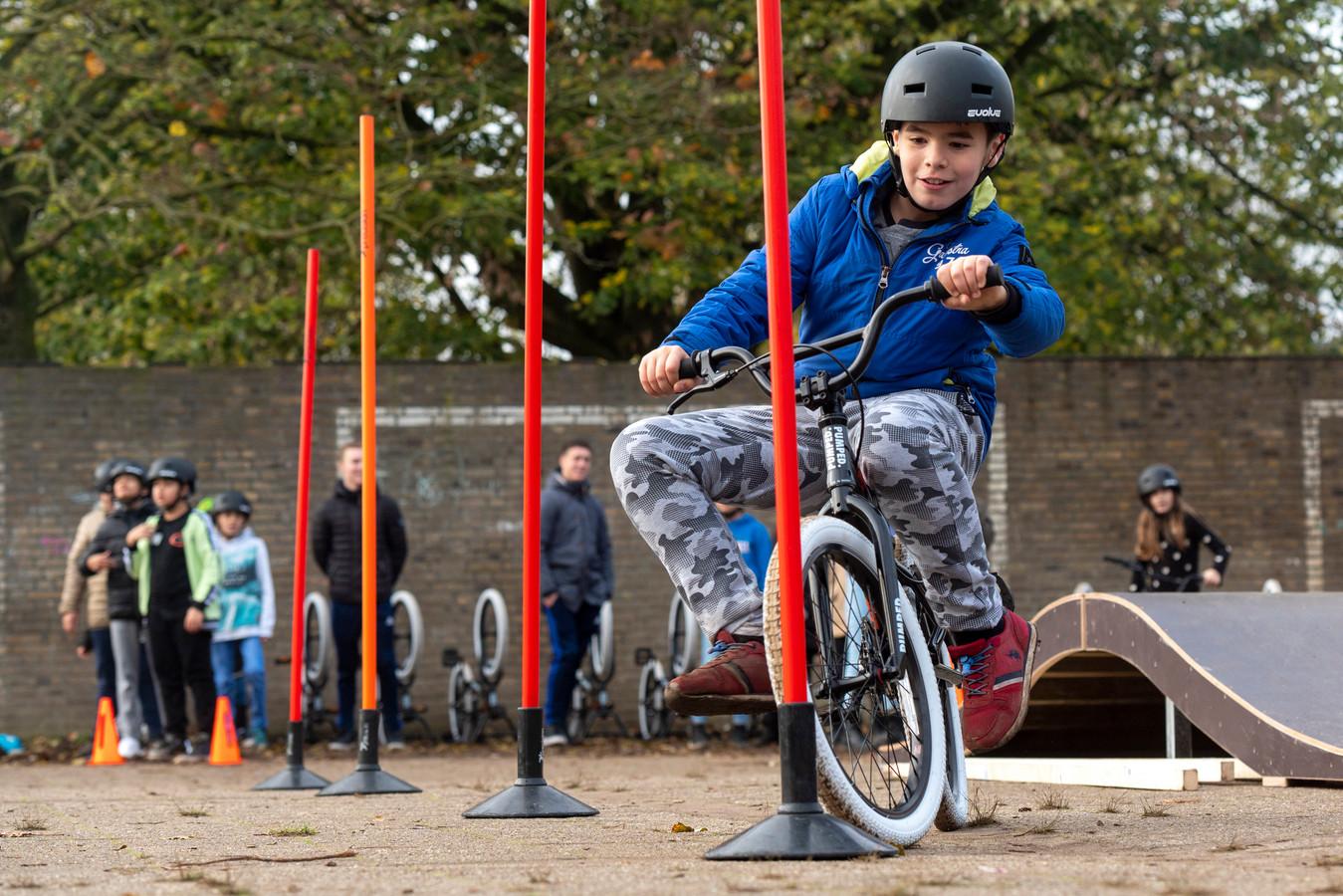 Slalommen tussen de paaltjes op de speelplaats van de Parkschool. Rechts op de foto een deel van de mobiele pumptrack, waarmee het Sportbedrijf Arnhem een rondtoer maakt langs de basisscholen.