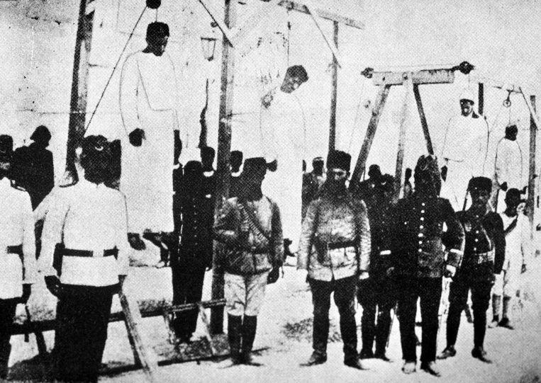 Turkse soldaten naast opgehangen lichamen van Armeense mannen in 1915.  Beeld AFP
