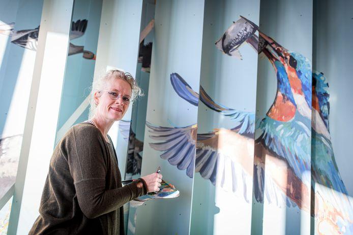 Janet Timmerije bezig met de ijsvogel op het buitenkunstwerk voor Eibergen. Tussen de panelen door is een glimp van de vliegende ganzen te zien.