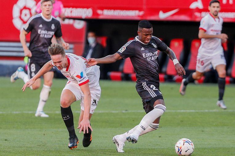 Sevilla-spits Luuk de Jong wordt afgetroefd door de latere matchwinnaar Vinicius Junior van Real Madrid (0-1).  Beeld AP