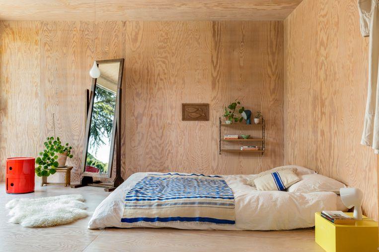 Een minimum aan meubels en van boven tot onder bekleed met pijnboomhout. Voor de slaapkamer lieten Wim en Valeria zich inspireren door typische Japanse interieurs.    Beeld Helenio Barbetta