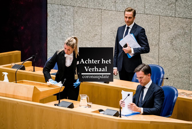 Een kamerbode maakt het spreekgestoelte schoon, minister Hugo de Jonge van Volksgezondheid, Welzijn en Sport (CDA) en premier Mark Rutte tijdens een debat over de ontwikkelingen rond het coronavirus.