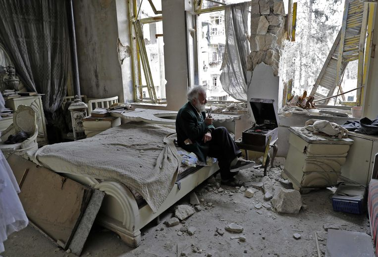 Mohammad Mohiedine Anis, 70, rookt zijn pijp en luistert platen in zijn verwoeste slaapkamer.  Beeld AFP