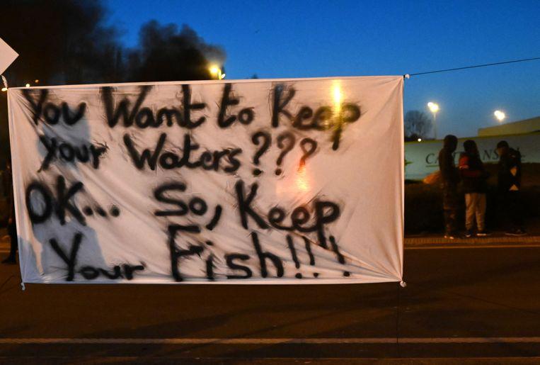 Franse vissers bij een spandoek met de tekst: 'dus jullie willen jullie wateren houden??? oké, maar houd jullie vis dan ook maar' bij een protestactie in Boulogne-sur-Mer. Beeld AFP