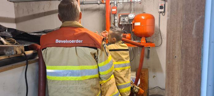 Brandweerlieden zijn druk bezig maandagmorgen in de kelder van de fietsenzaak in Staphorst.