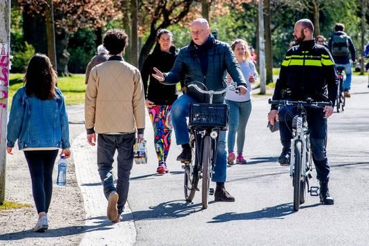 Justitieminister Ferd Grapperhaus ging eerder met de politie mee tijdens een fietstocht door het Vondelpark en sprak mensen aan als ze te dicht naast elkaar liepen.