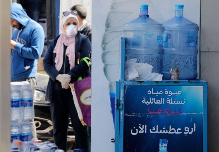 Mensen staan in de rij bij een kleine supermarkt in Amman, de hoofdstad van Jordanië. Na vijf dagen volledige lockdown, heeft de regering besloten apotheken, kleine supermarkten, bakkerijen en winkels die water verkopen weer te openen.  Beeld EPA