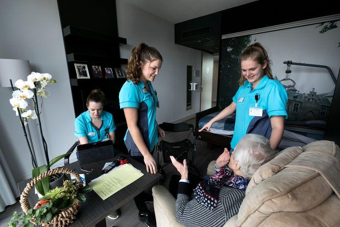 Drie leerling-verzorgenden aan de slag in zorghotel Vitassist in Helmond. Tessa Vorstenbos, Evi Claessens en Rachel van Eemeren (vlnr) helpen de 92-jarige mevrouw Maria Visser.
