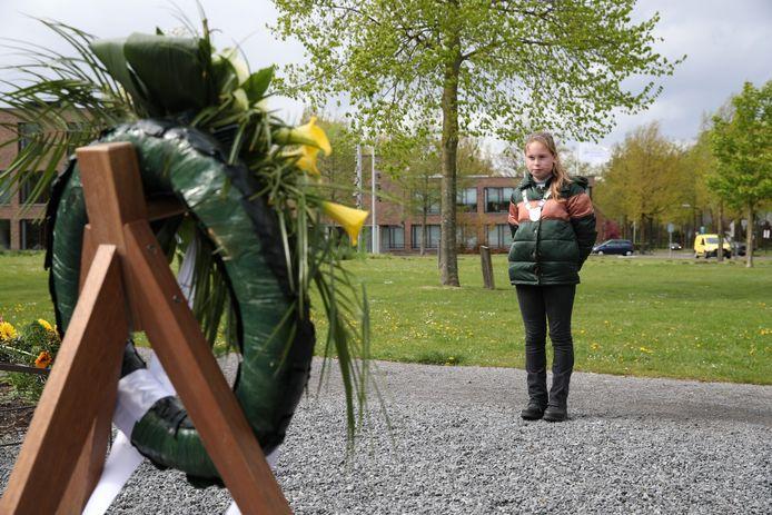 Kinderburgemeester Kiki Kemps legt een krans bij het monument in Beek en Donk