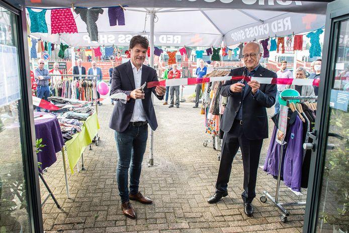 Burgemeester Paul Depla knipt samen met de voorzitter van het Rode Kruis Midden en West-Brabant Piet van den Bosch het befaamde lintje door.