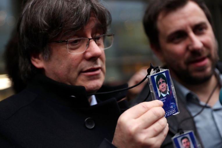 De vroegere regiopresident van Catalonië, Carles Puigdemont, toont zijn tijdelijke accreditatie voor het Europees Parlement in Brussel. Rechts Toni Comín met de zijne. Beeld AP