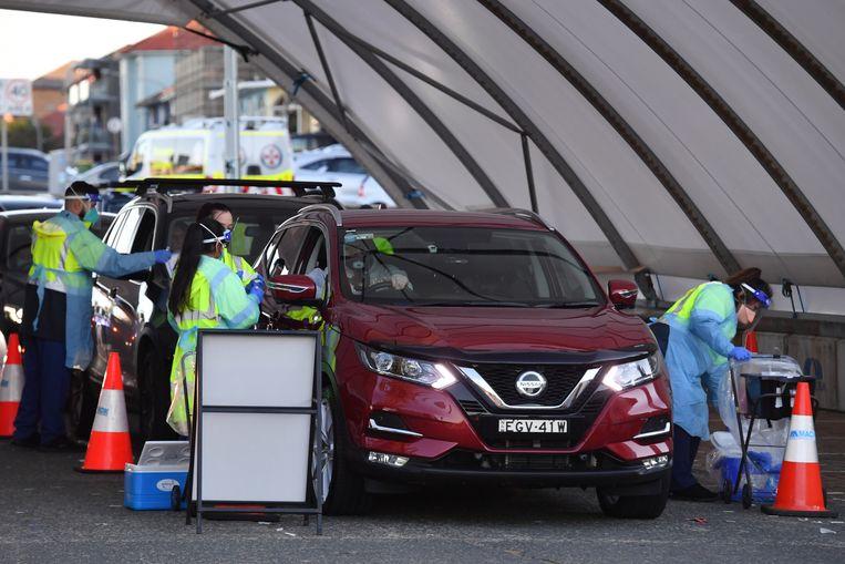 Mensen laten zich testen in een drive-in-testcentrum in Sydney. Beeld EPA