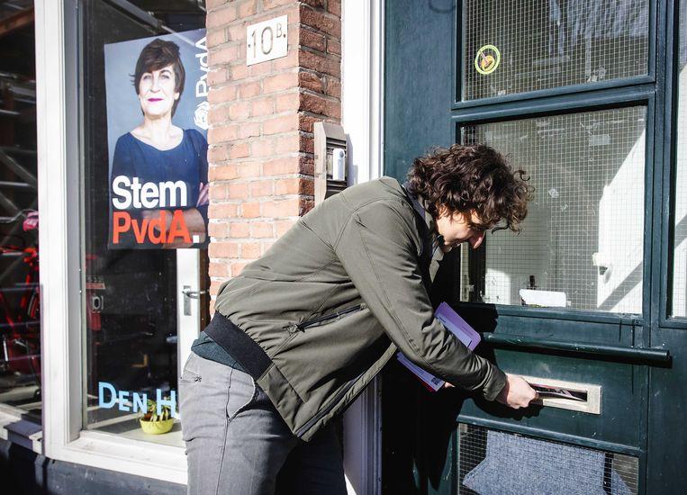 Lijsttrekker Jesse Klaver van GroenLinks doet een flyer in de brievenbus van het Haagse kantoor van de PvdA.   Beeld ANP
