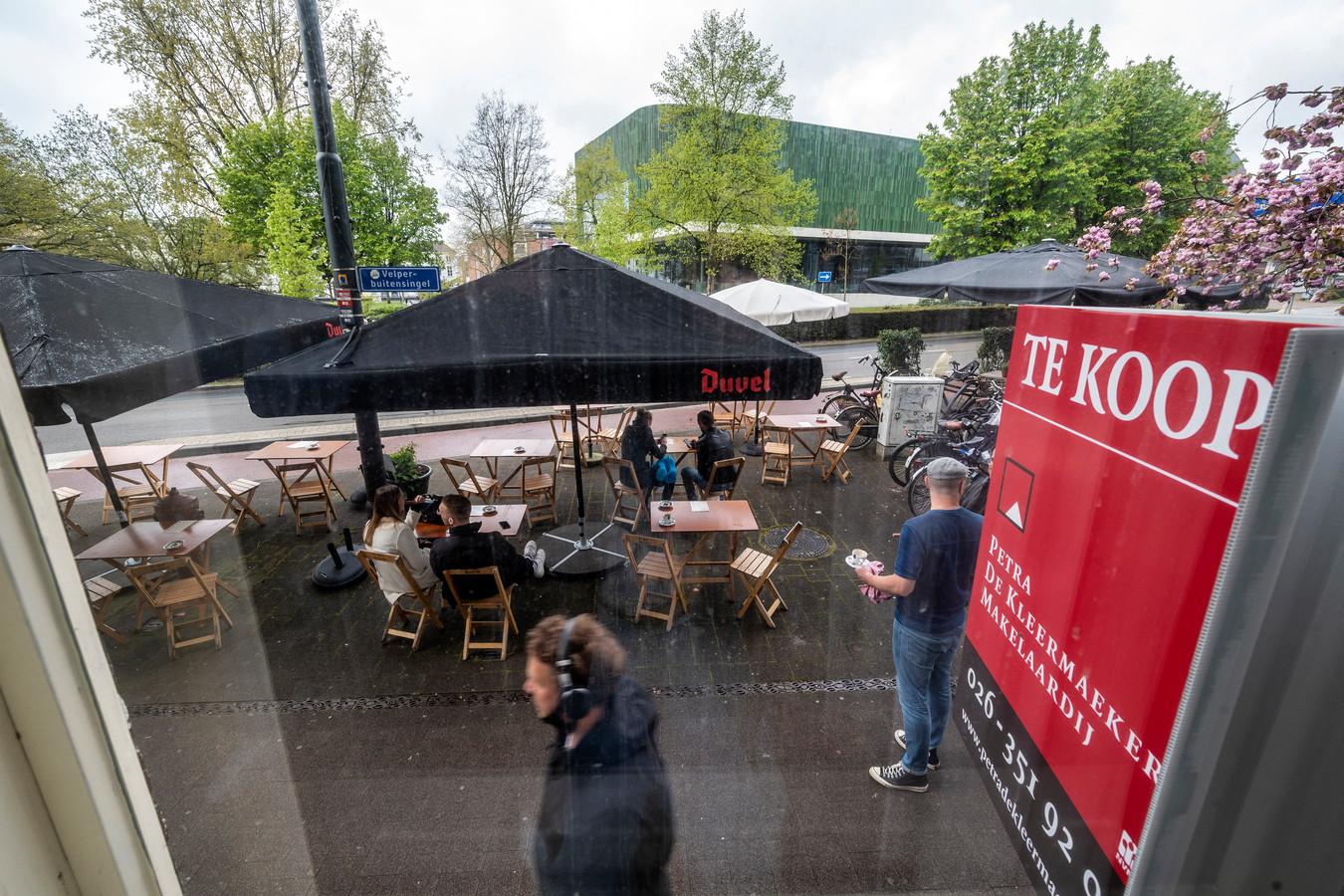 Het uitgebreide coronaterras van Café Vrijdag pal voor het te koop staande herenhuis van Xandra Derks.