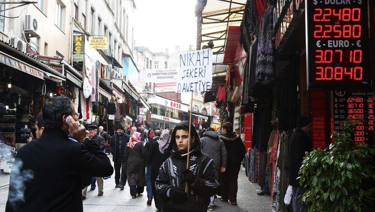Turken lopen langs een geldwisselkantoor in Instanboel Beeld afp