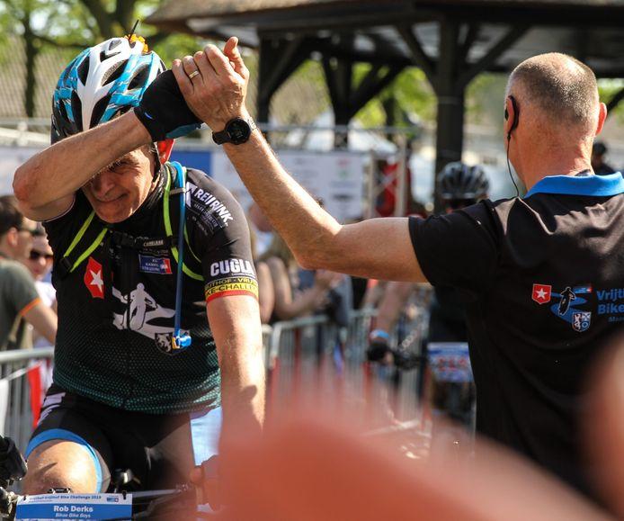 Rob Derks schiet vol bij de finish van de Vrijthof Bike Challenge als hij Aldwin van Gils de hand schudt.