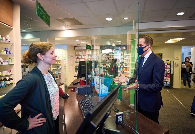 Demissionair minister Hugo de Jonge (VWS) schaft een zelftest aan bij een apotheek. Beeld ANP