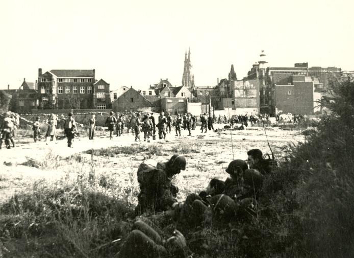 Amerikaanse militairen lopen tijdens de bevrijding van Eindhoven op 18 september 1944 over een kale vlakte waar ooit de Demer was.