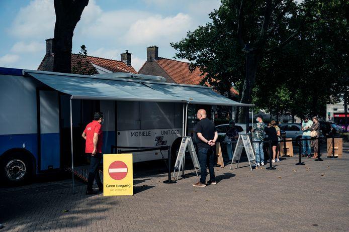 Drukte bij de mobiele prikbus van de GGD zondagochtend op het Kerkplein in Leuth.