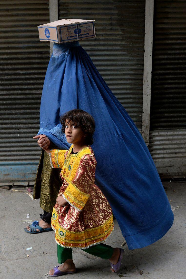 Een moeder wandelt met haar kind over straat in Kaboel. Beeld AFP