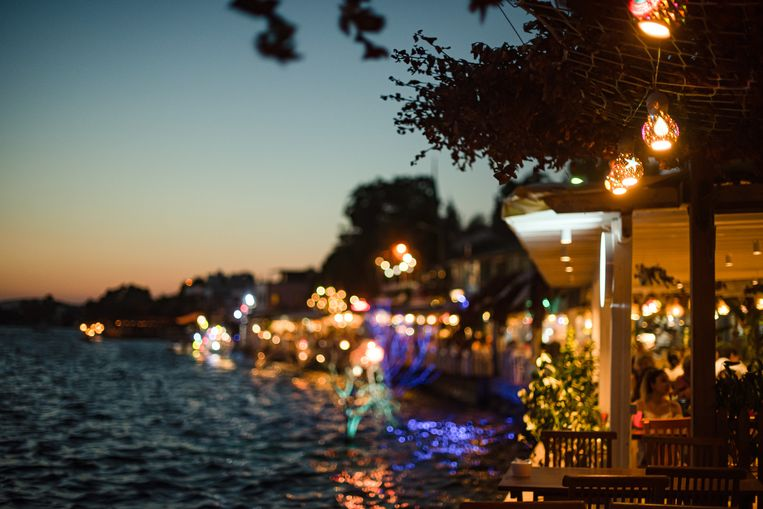 Seaside Restaurants With Colorful Lights on Summer Evening Beeld Getty Images/iStockphoto