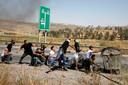 Palestijnse demonstranten gooien stenen naar Israëlische soldaten nabij Nablus.
