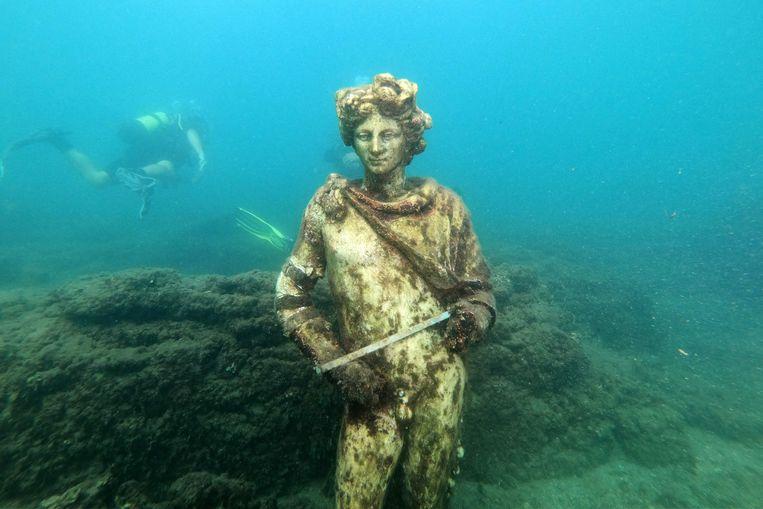 Toeristen nemen onder leiding van een gids een duik terug in de tijd, in het archeologische onderwaterpark van Baia, vlak bij de Italiaanse stad Napels. Dit beeld van Dionysus sierde ooit een van de Romeinse villa's in de kustplaats, maar is inmiddels net als Baia in de golven verdwenen. Beeld AFP