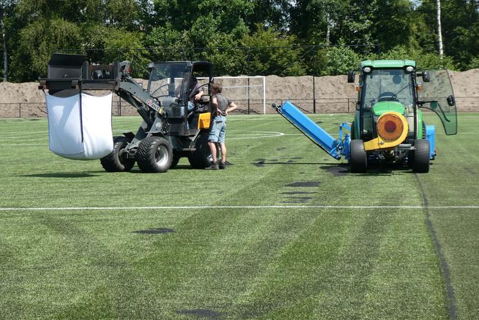 Met een speciale stofzuigertraktor worden 'big bags' gevuld met rubber korrels op het terrein van sportpark Heidelust in Gestel.