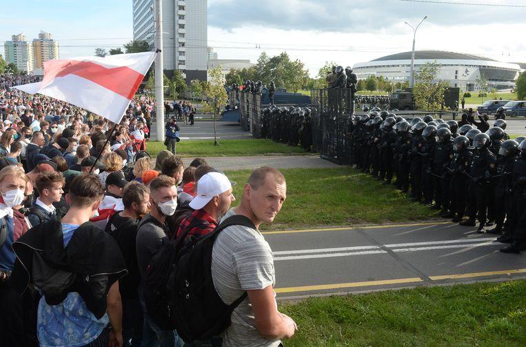 Een bijna dagelijks beeld in Minsk: demonstranten tegenover het leger.  Beeld EPA