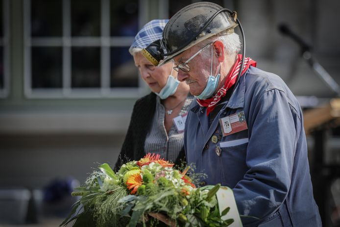 Enkele mijnwerkers legden bloemen neer als eerbetoon voor de meer dan 900 slachtoffers die stierven in de mijnen.