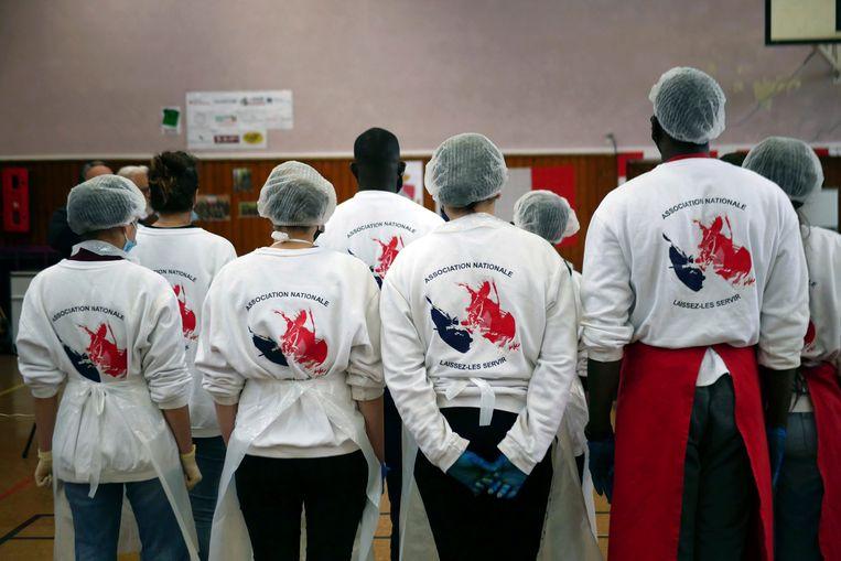 Leden van Laissez-Les Servir worden gebriefd tijdens de 40-daagse Marathon van Solidariteit, waarbij ze honderden maaltijden per dag maken voor mensen in Pierrefitte-sur-Seine. Beeld Thibault Camus / AP