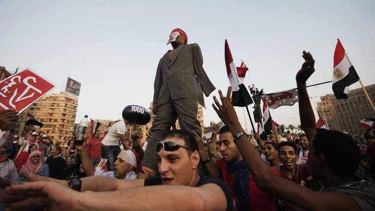 Demonstranten op het Tahrirplein hebben een pop als president Morsi gemaakt die ze over het plein dragen Beeld AFP