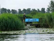 Met spandoeken langs het water vraagt stichting schippers hun snelheid te matigen: 'Geef ons rust'