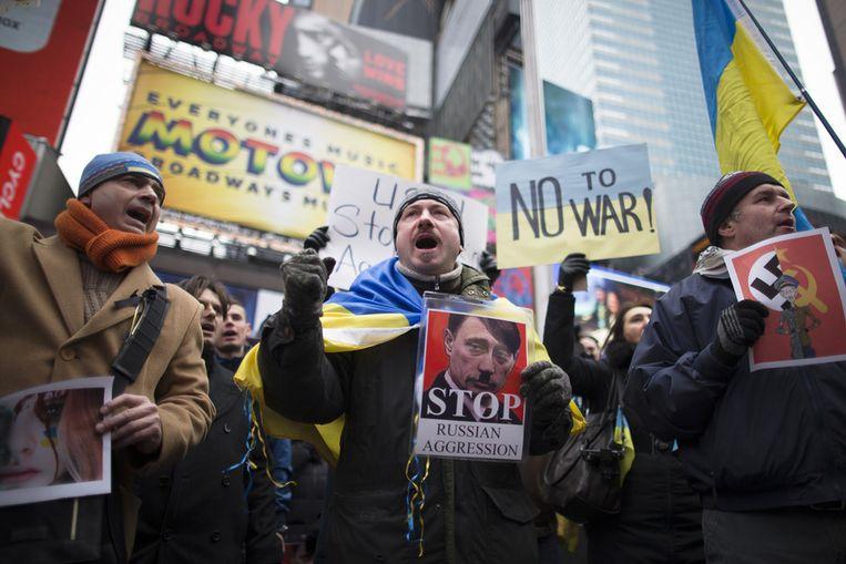 Demonstranten tegen de Russische militaire acties in Oekraïne op Times Square in New York. Beeld ap