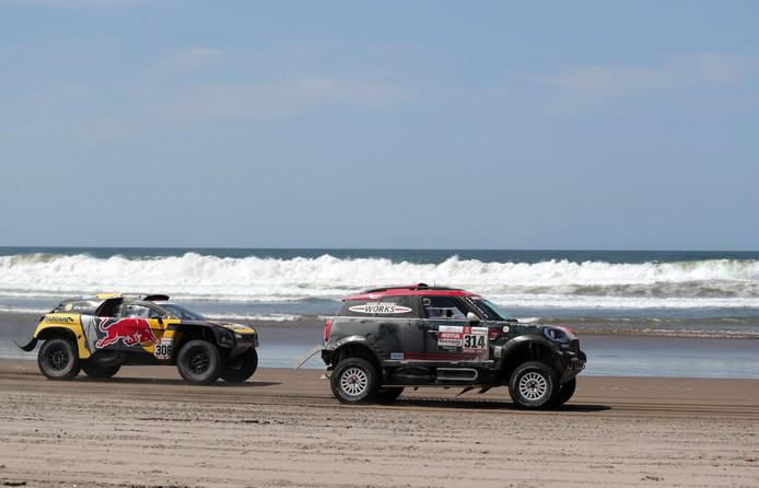Dagwinnaar Sébastien Loeb (l) volgt in het spoor van de Mini van Yazeed Al Rajhi tijdens de 5e etappe van de Dakar Rally in Peru.