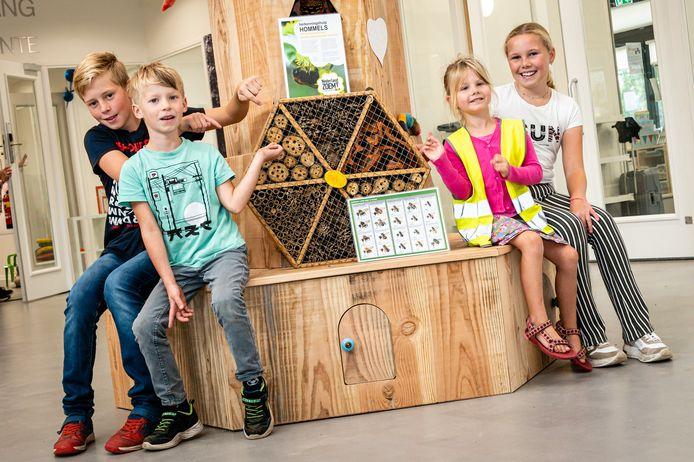 Leerlingen van het kindcentrum in Markelo bij het insectenhotel dat ze van vrijwilligers van Machtig Mooi Markelo Zoemt kregen. Het hotel heeft de vorm van een honingrat ien is gemaakt door Bennie Schreurs.