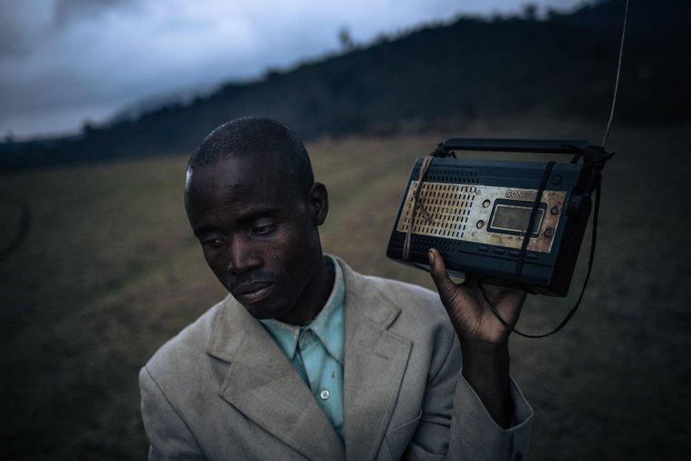Een man die moest vluchten voor het geweld in Oost-Congo luistert naar het laatste nieuws.  Beeld AFP