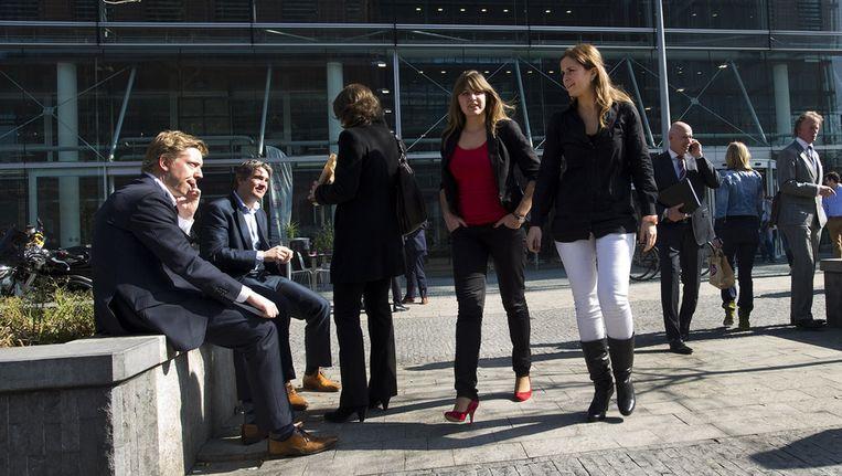 Werknemers lunchen in de pauze buiten in de zon rond het Amsterdamse WTC. Vrouwen hebben vaak een deeltijdbaan en zijn daardoor financieel afhankelijk van hun man of familie Beeld ANP