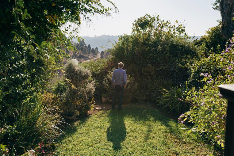 David Grossman in zijn tuin. 'Wat kan ik doen? Blijven schrijven. Zo helder mogelijk, in deze duistere tijd.' Beeld Jonas Opperskalski / laif