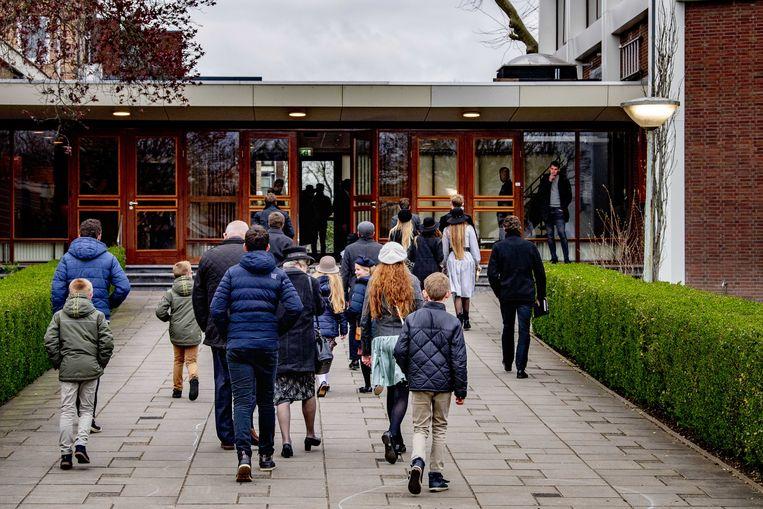 Kerkgangers komen aan bij de Mieraskerk voor de kerkdienst op Goede Vrijdag. De veelbesproken en beveiligde Mieraskerk in Krimpen aan den IJssel zet de deuren open voor alle gelovigen in aanloop naar Pasen. Beeld ANP