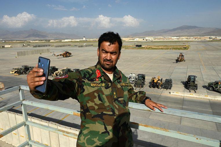 Een soldaat van het Afghaans regeringsleger maakt een selfie bij de achtergelaten luchthaven Bagram, de grootste VS-basis in Afghanistan die de Amerikanen plotsklaps hebben verlaten. Beeld AFP