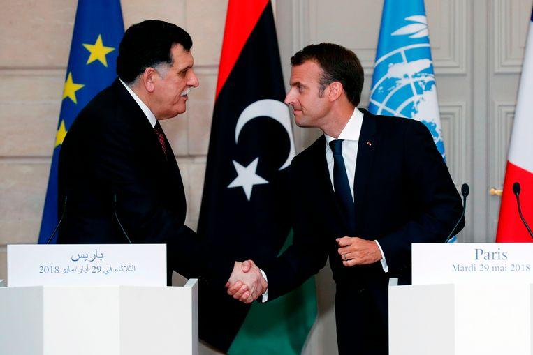 De Libische premier Fayez al-Sarraj en de Franse president Emmanuel Macron schudden elkaar de hand. Beeld AFP
