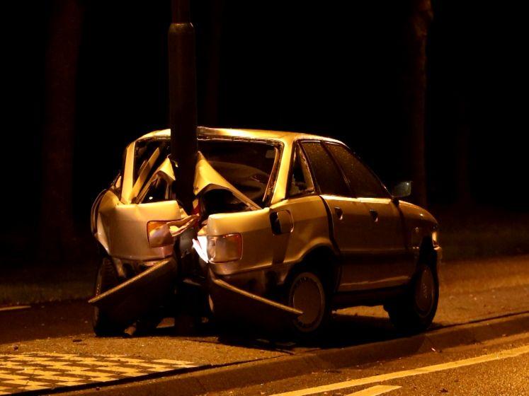 Auto slipt en botst achterstevoren op lichtmast