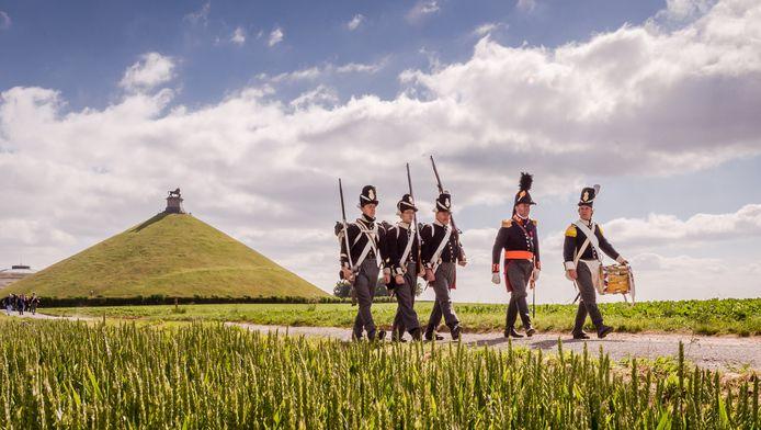 Deelnemers aan de reënscenering van de Slag poseren nabij de Leeuw van Waterloo.