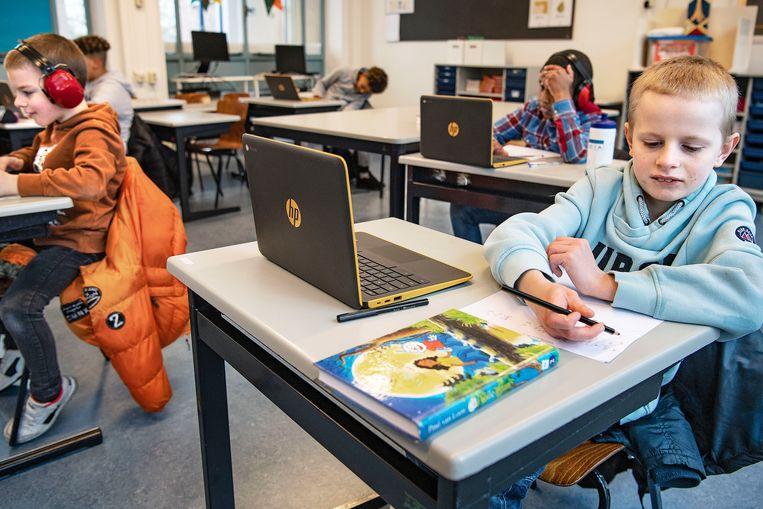Kinderen van de basisschool Finlandia werken geconcentreerd op hun laptops tijdens noodopvang.  Beeld Guus Dubbelman / de Volkskrant