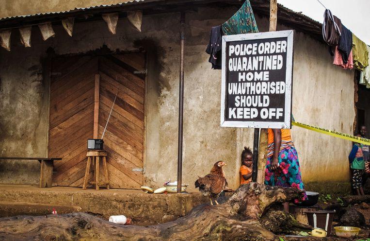 Een huis in Sierra Leone dat onder quarantaine is geplaatst, omdat familieleden besmet waren met ebola. Beeld AP