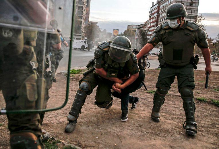 Chileense politieagenten grijpen een demonstrant tijdens een protest in Santiago.  Beeld AFP