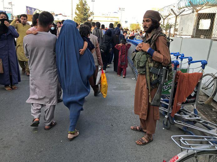 Een strijder van de taliban houdt de wacht terwijl mensen richting de luchthaven van Kabul stappen.
