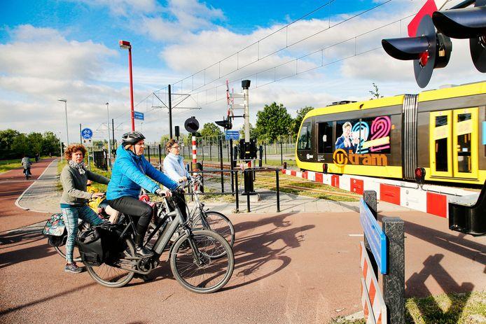 Fietsers wachten bij spoorbomen op de Koningsweg terwijl de testrit van de Uithoflijn langsrijdt.